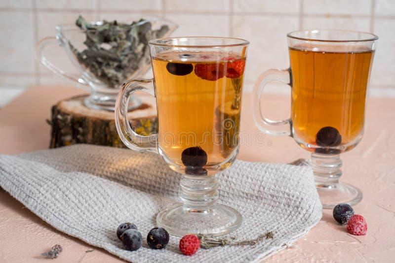 чай черной смородины с зелеными листьями в стеклянной чашке в осени на предпосылке окна с дождевыми каплями на белое деревянном стоковые фотографии rf