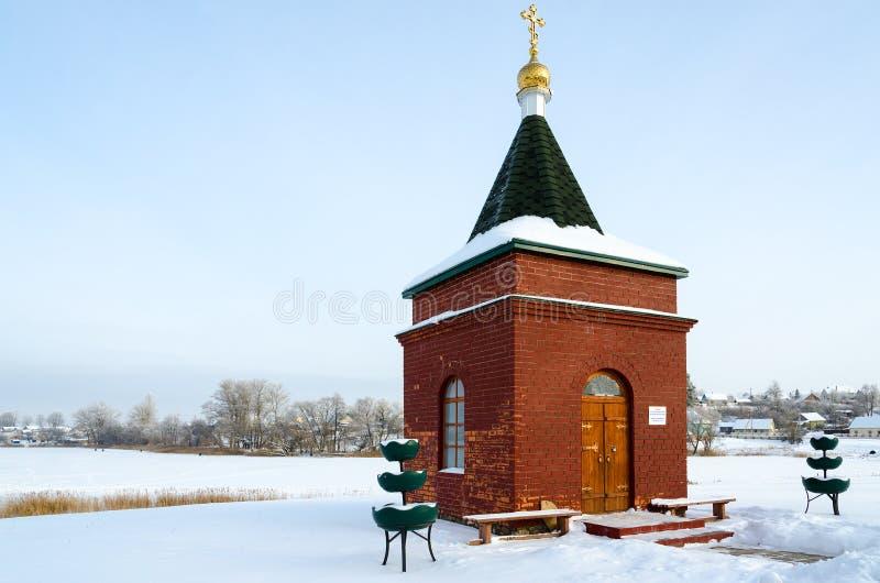 Часовня в честь благословленного Matrona Москвы на банке покрытого снег озера, ландшафта зимы, Senno, Беларуси стоковые изображения rf