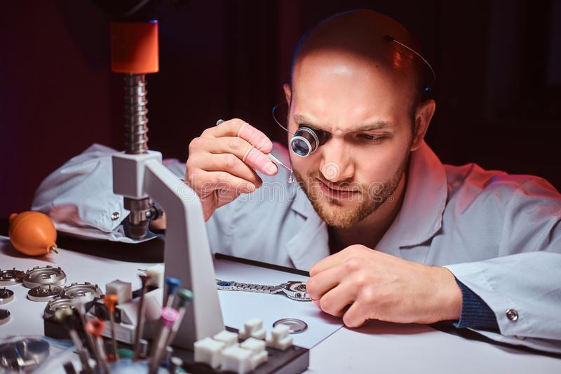 Часовщик Expirienced делает гравировку для дозора custmer на его мастерской стоковые фотографии rf