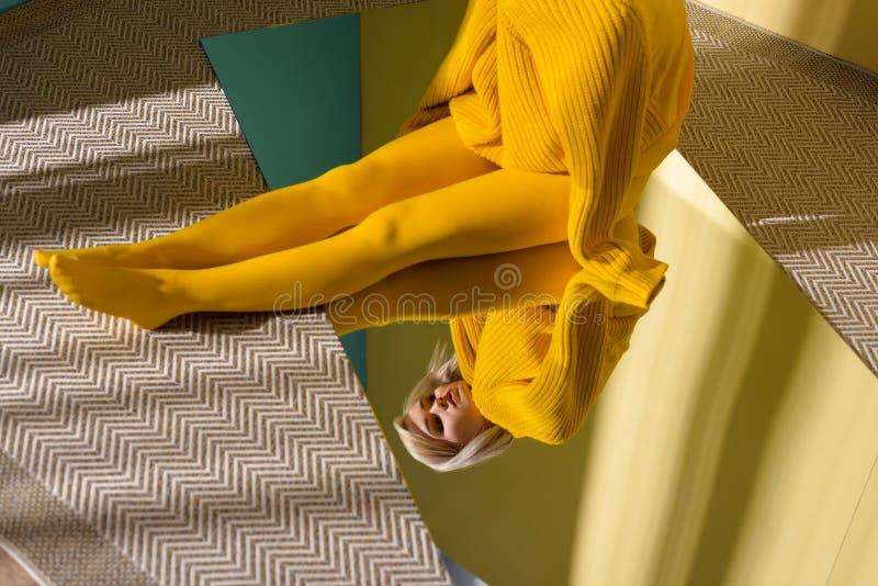 частично взгляд женщины в желтом свитере и колготках сидя на зеркале с отражением стоковые изображения rf