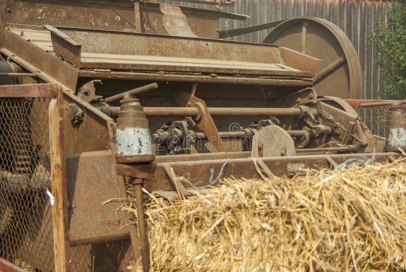 Частично взгляд исторический молотить - машина в деятельности с шариком соломы на переднем плане стоковые изображения rf