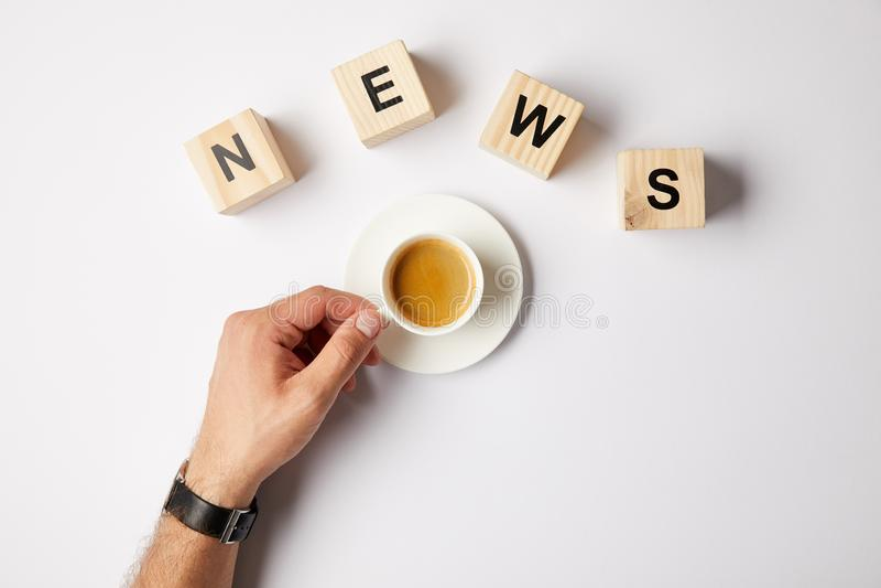 частично взгляд персоны с чашкой кофе и слово новостей слова сделанное из деревянных блоков алфавита, на белой предпосылке стоковые изображения