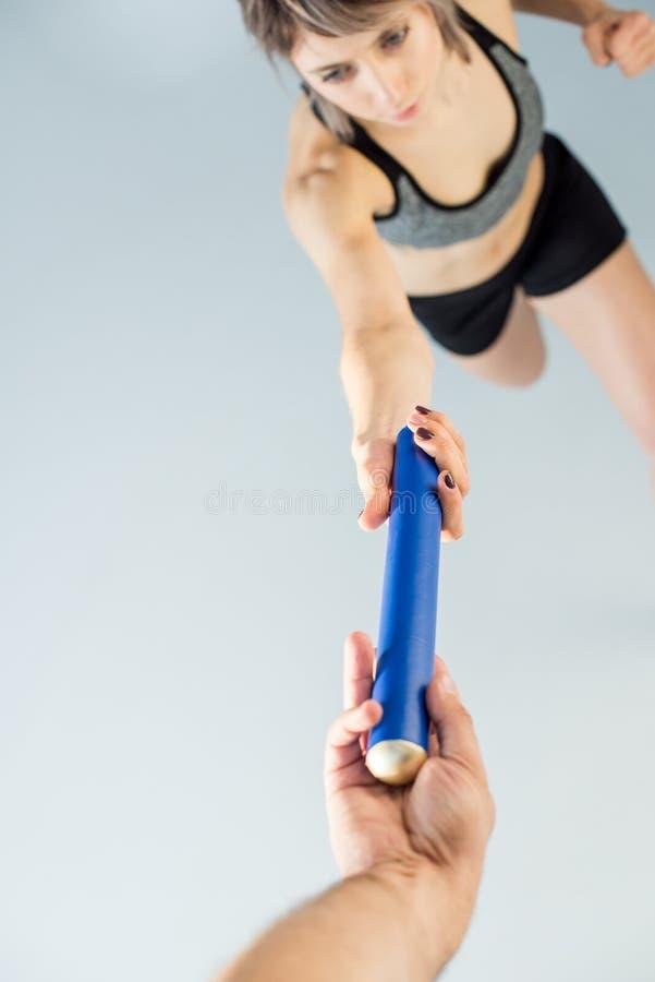 Частично взгляд спортсменки передавая жезл реле к партнеру стоковое изображение