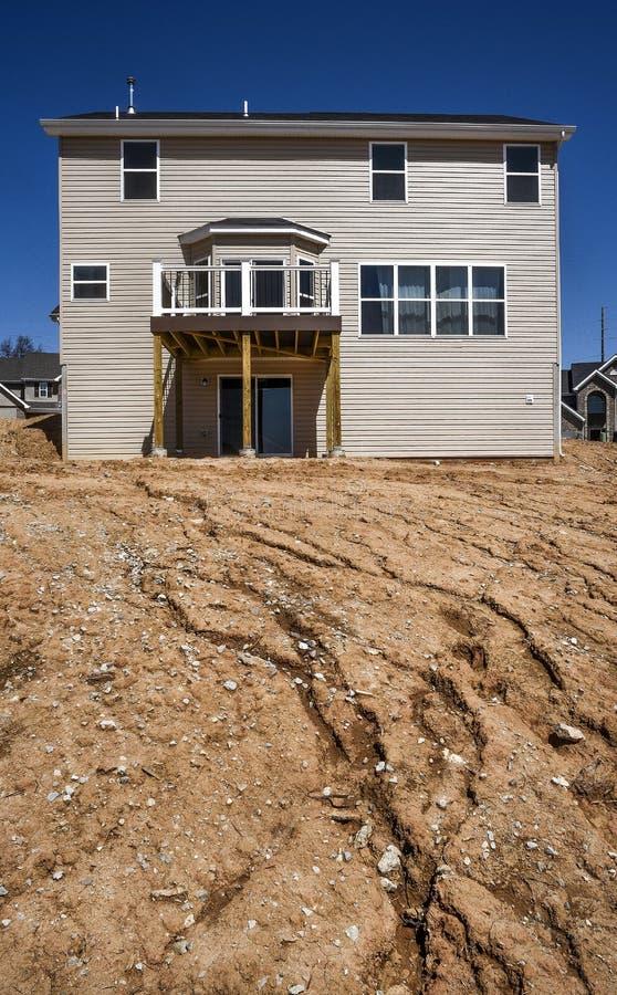 Частично законченный новый двухэтажный дом под конструкцией в жилом подразделении с тинными холмом, siding винила и окнами стоковое изображение