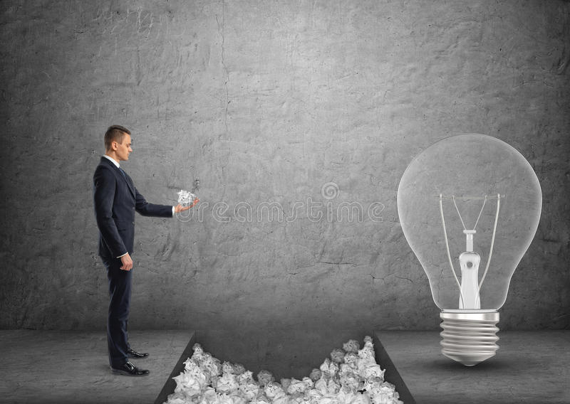 Части бизнесмена бросая скомканной бумаги к зазору между им и большой электрической лампочкой стоковые фотографии rf