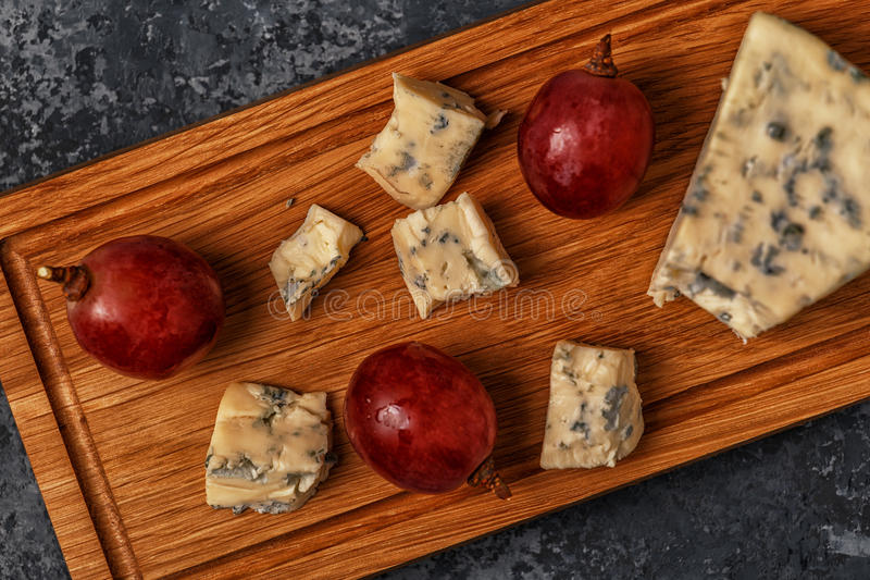 Части голубого сыра на деревянной сервировке всходят на борт стоковое фото