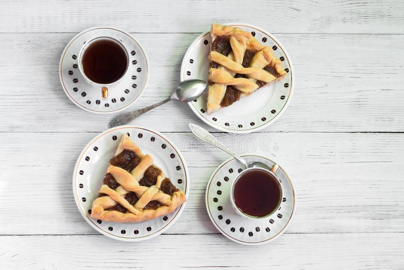 Части душистого пирога тыквы на деревянном столе с чашками кофе стоковое изображение