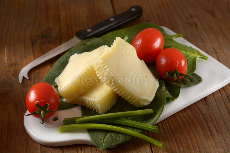Части итальянского соленого сыра с томатом вишни в разделочной доске стоковые изображения