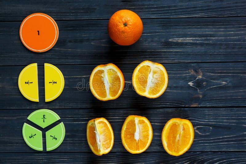 Части и апельсины математики Сolorful как образец на темных деревянных предпосылке или таблице Интересная творческая смешная мате стоковое фото
