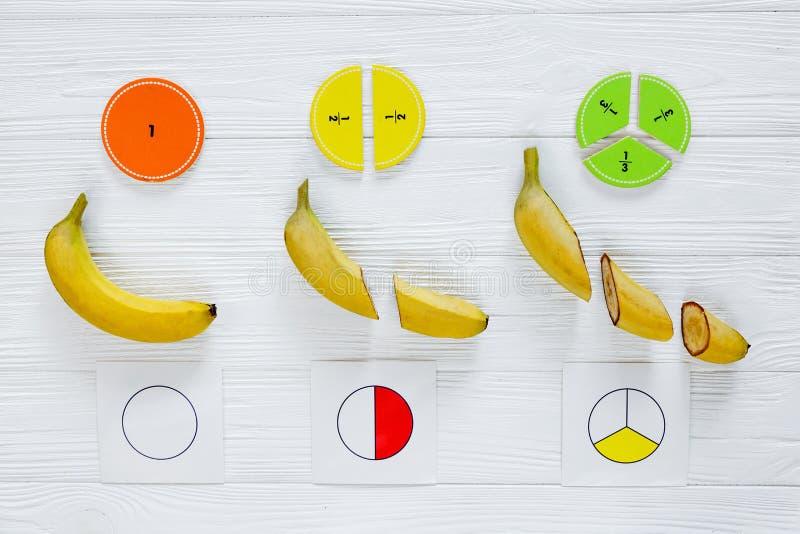 Части и бананы математики Сolorful как образец на белых деревянных предпосылке или таблице Интересная математика для детей E стоковые изображения rf