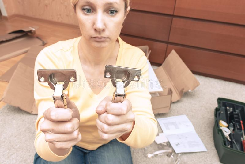 Части одиночной молодой женщины собирая новой мебели и удержания 2 деталей мебели, она смущена, открытые коробки с стоковое фото