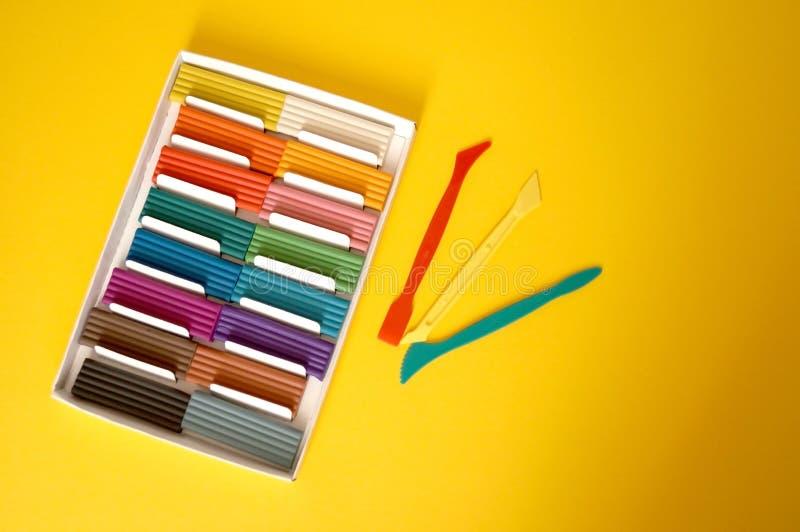 Части пестротканого пластилина для детей против желтой предпосылки стоковое изображение