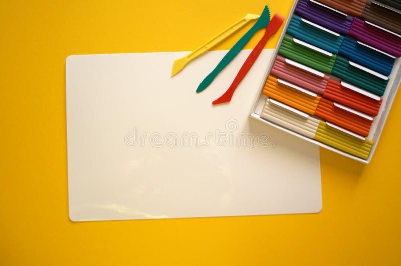 Части пестротканого пластилина для детей против желтой предпосылки стоковая фотография