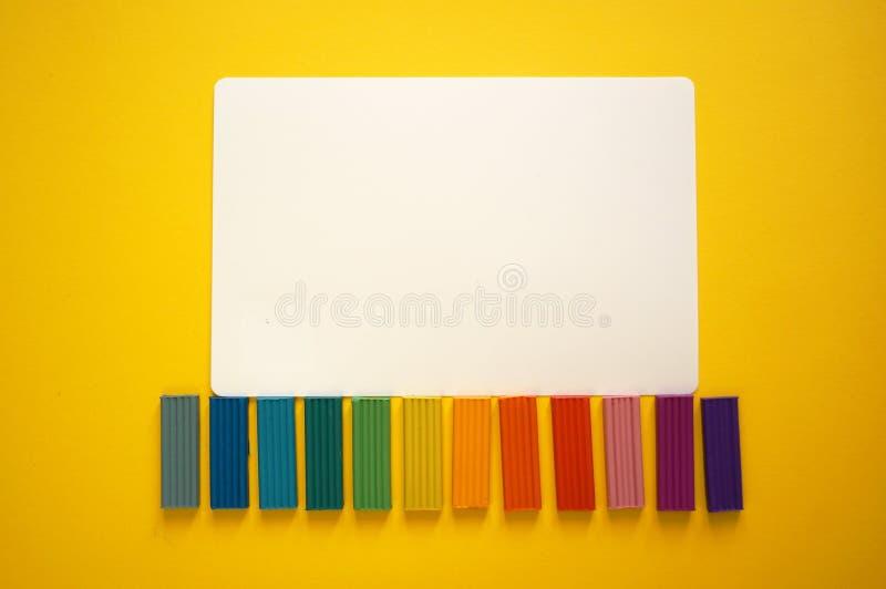 Части пестротканого пластилина для детей против желтой предпосылки стоковые изображения