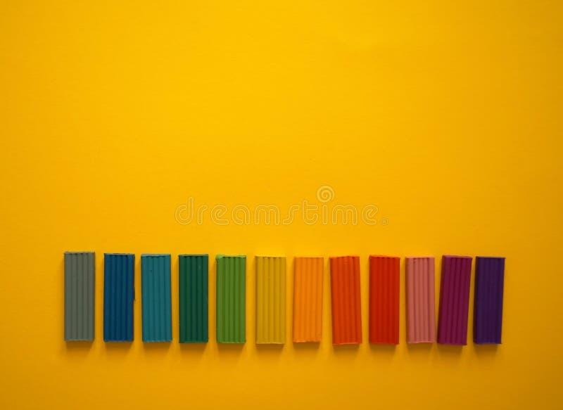 Части пестротканого пластилина для детей против желтой предпосылки стоковое фото