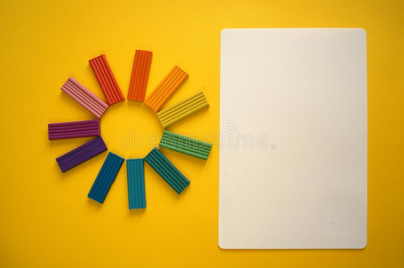 Части пестротканого пластилина для детей против желтой предпосылки стоковое изображение rf