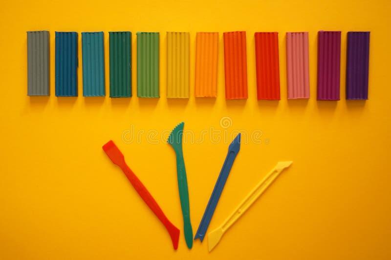 Части пестротканого пластилина для детей против желтой предпосылки стоковые изображения rf