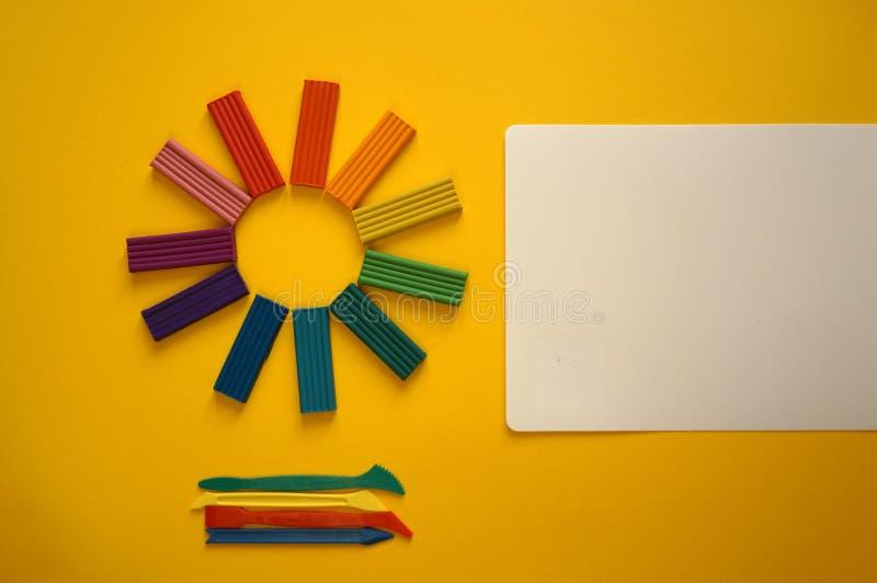Части пестротканого пластилина для детей против желтой предпосылки стоковые фотографии rf