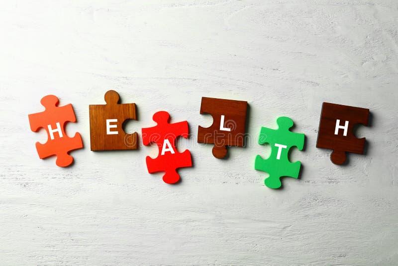 Части слова составленного головоломкой ЗДОРОВЬЯ на белой деревянной предпосылке стоковая фотография