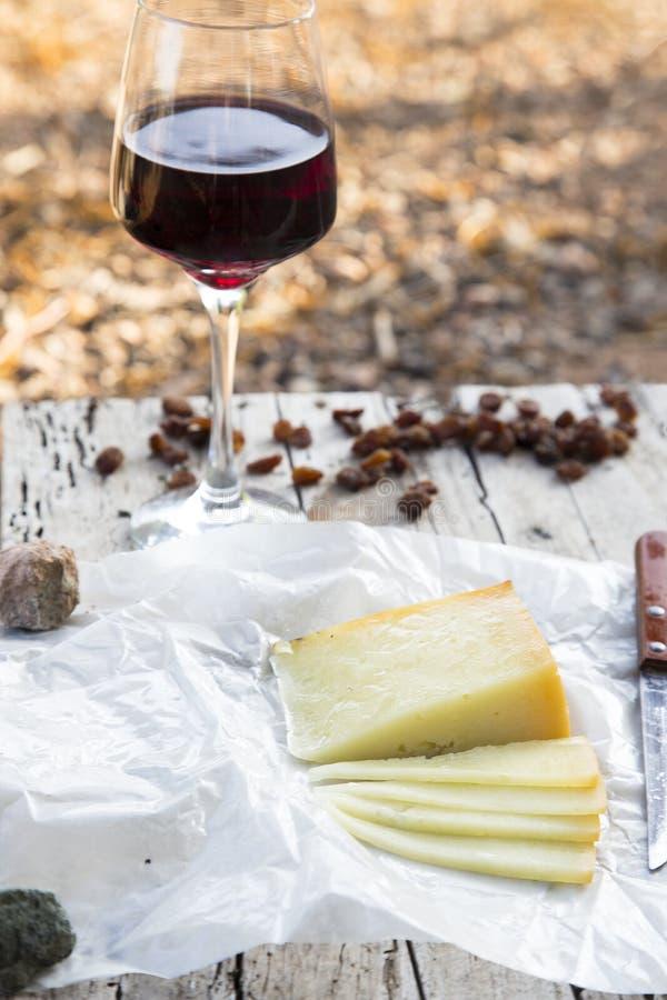 Части сыра и изюминок с красным бокалом на старой деревянной доске стоковое фото