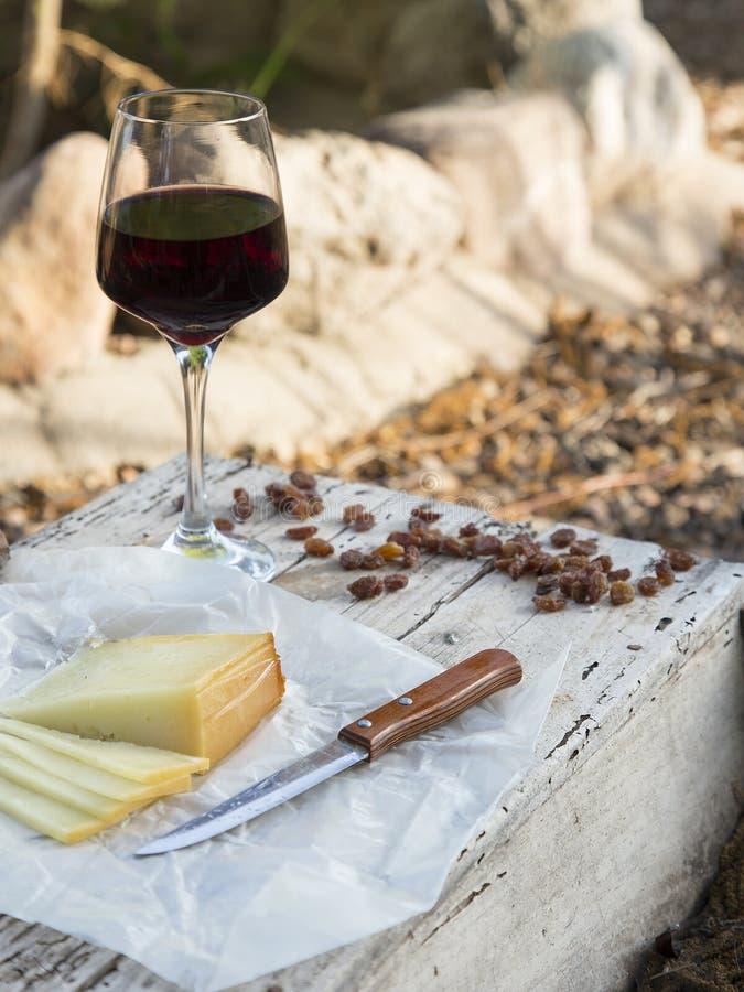 Части сыра и изюминок с красным бокалом на старой древесине стоковые изображения rf