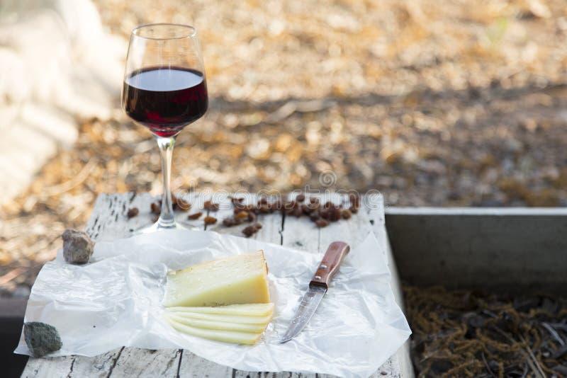 Части сыра и изюминок с красным бокалом на старой древесине стоковое фото rf
