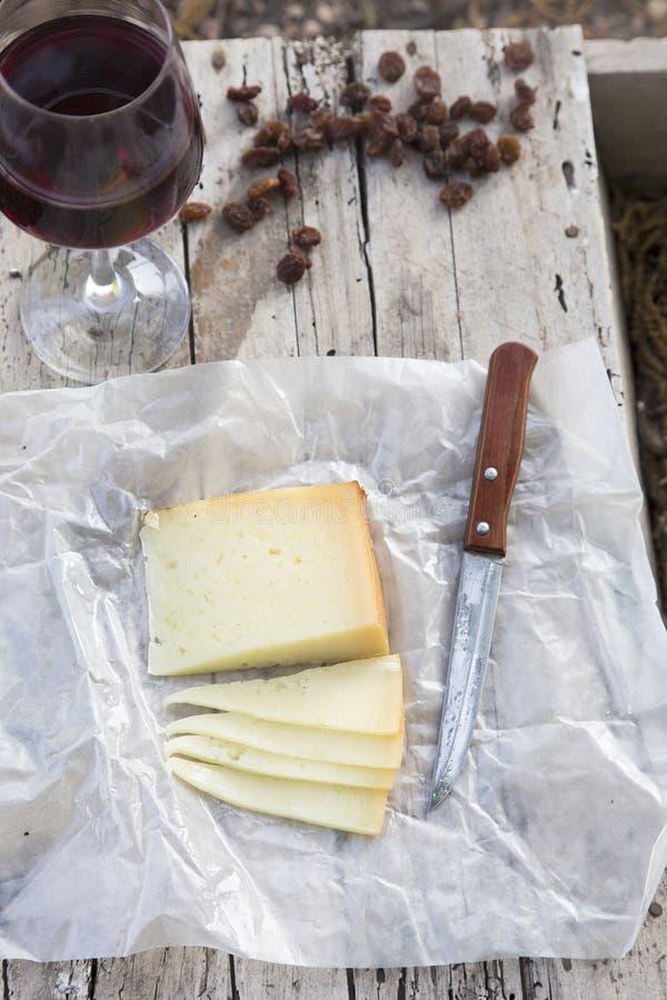 Части сыра и изюминок с красным бокалом на старой древесине стоковая фотография rf
