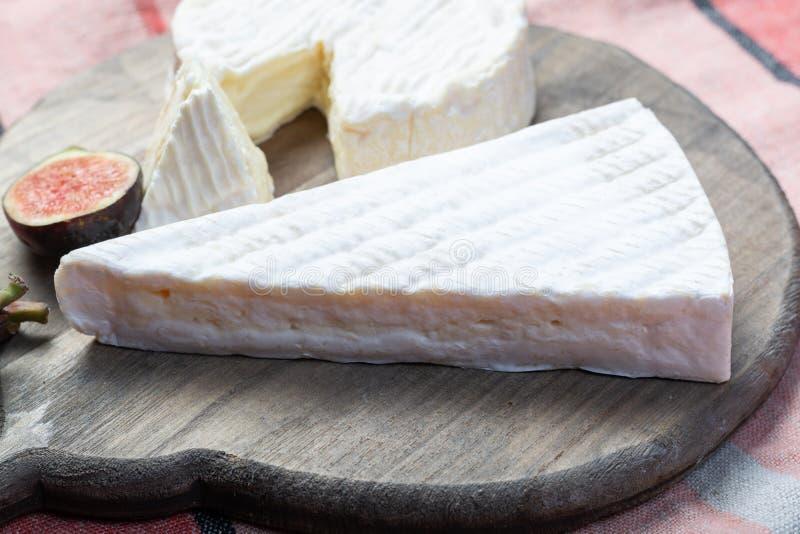 2 части французских мягких сыров бри и камамбера с белой прессформой и сильным запахом, служили со свежими зрелыми смоквами стоковая фотография