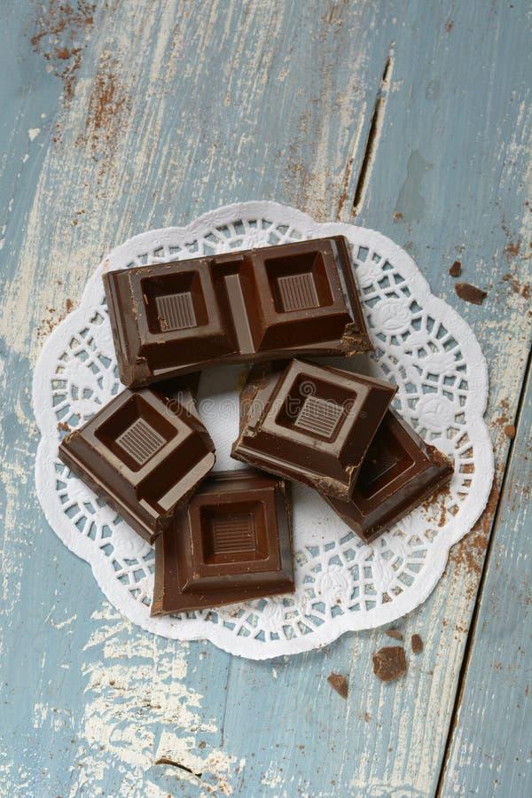 Части шоколада на голубом деревянном столе стоковые фото