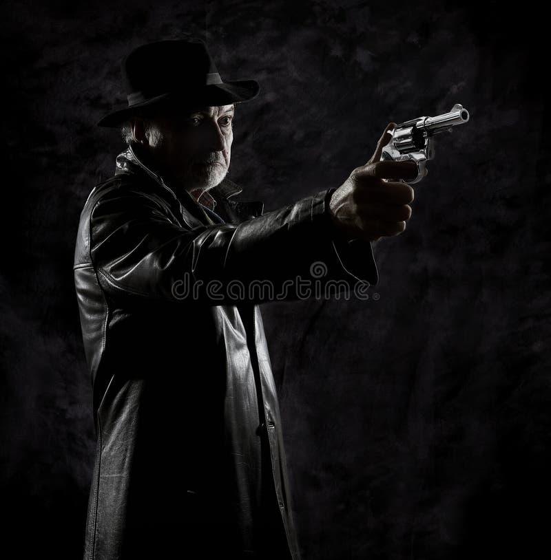 Частный детектив с револьвером перед черным фоном стоковое изображение