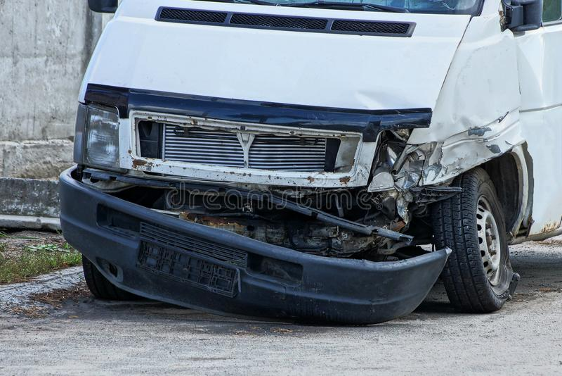 Часть белой шины после аварии с сломленными бампером и фарой на дороге стоковое фото