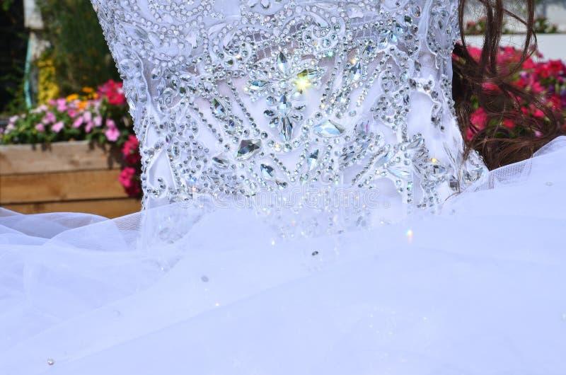Часть белого платья невесты с вышивкой шариков стоковые фото