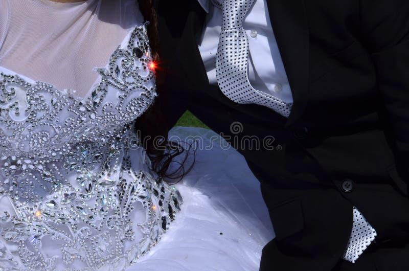 Часть белого платья невесты с embroideryand шариков куртка жениха с рубашкой и связью стоковые фотографии rf