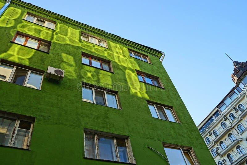 Часть большого зеленого дома с много окон на небе стоковые фото