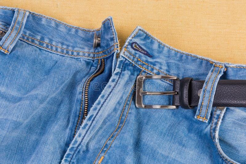 Часть верхней части голубых джинсов с черным поясом стоковые фотографии rf