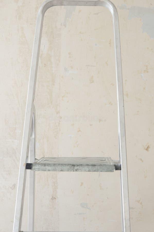 Часть грязной алюминиевой лестницы на фоне белой стены стоковое фото rf