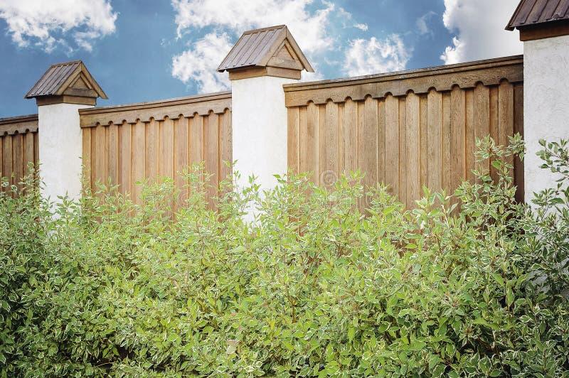 Часть деревянной коричневой современной загородки со столбцами законченными с камнем, конец-вверх Идеи загородки современного диз стоковые изображения