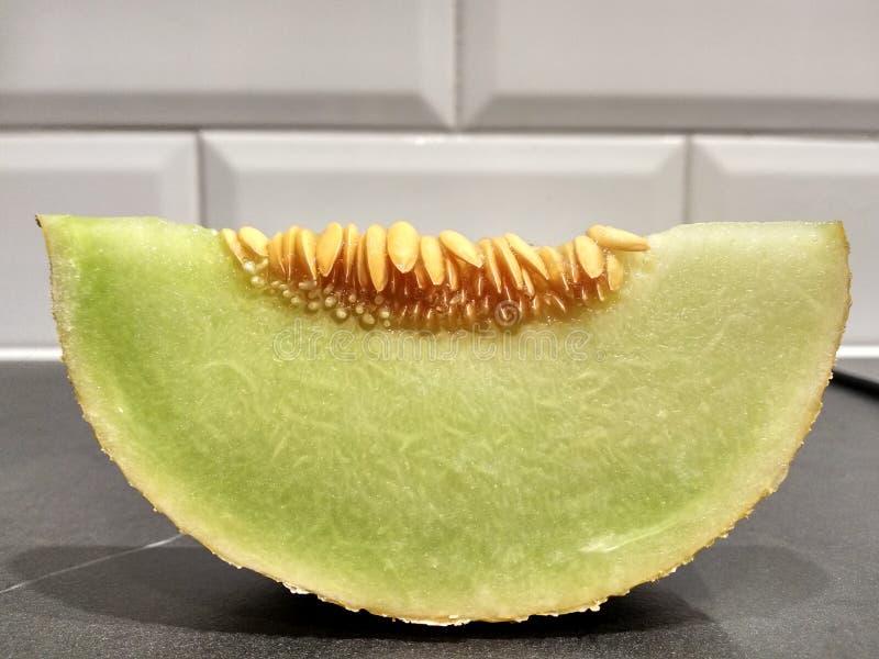 Часть дыни с семенами на таблице, отрезала зеленый цвет дыни белый против белой кирпичной стены стоковое фото rf