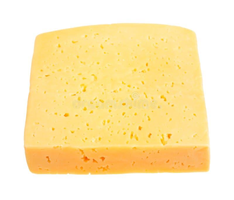 Часть желтого среднетвердого изолированного сыра стоковое фото