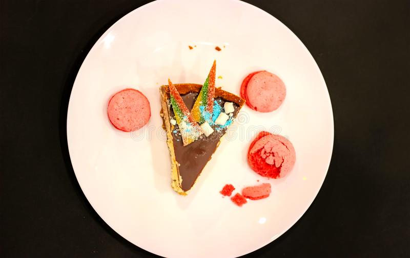 часть именниного пирога для моего дня рождения с свечой на розовой плите на черной таблице стоковое изображение