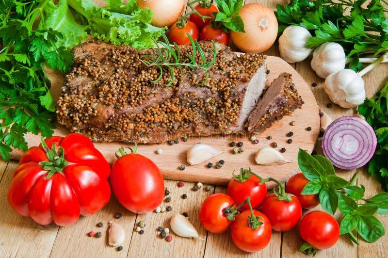 Часть испеченной говядины с свежими овощами на деревянном столе стоковое изображение rf