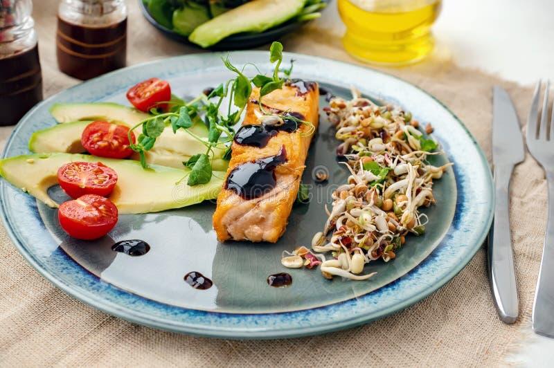Часть испеченных красных рыб с гарниром ростков и салата авокадоа Macrobiotic концепция еды E стоковое фото rf