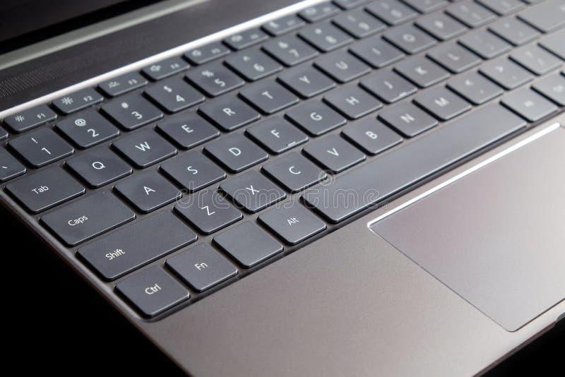 Часть клавиатуры компьтер-книжки и сенсорная панель раскрытой компьтер-книжки изолированной на черном взгляде со стороны стоковое изображение