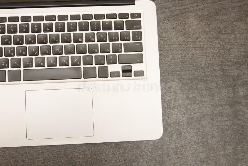 Часть клавиатуры компьтер-книжки на черном деревянном столе workplace стоковое фото rf