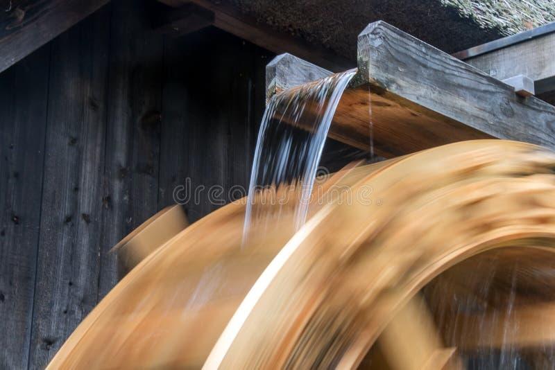 Часть колеса мельницы вращает под потоком воды, стоковые изображения rf