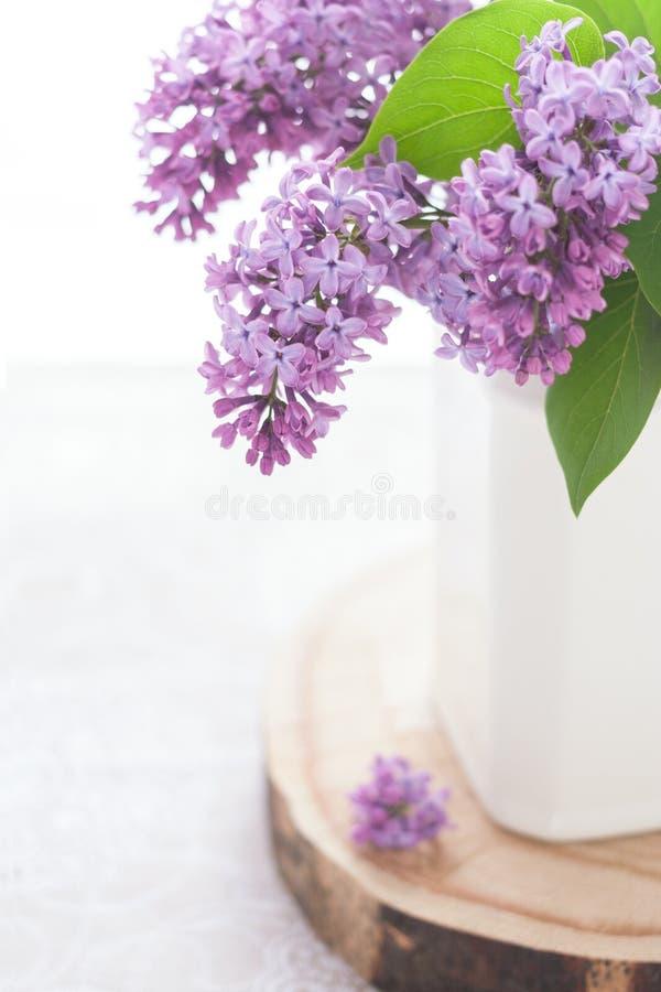 Часть конца-вверх белого керамического бака при фиолетовая зацветая сирень стоя на деревянной круглой доске, на таблице стоковое фото rf