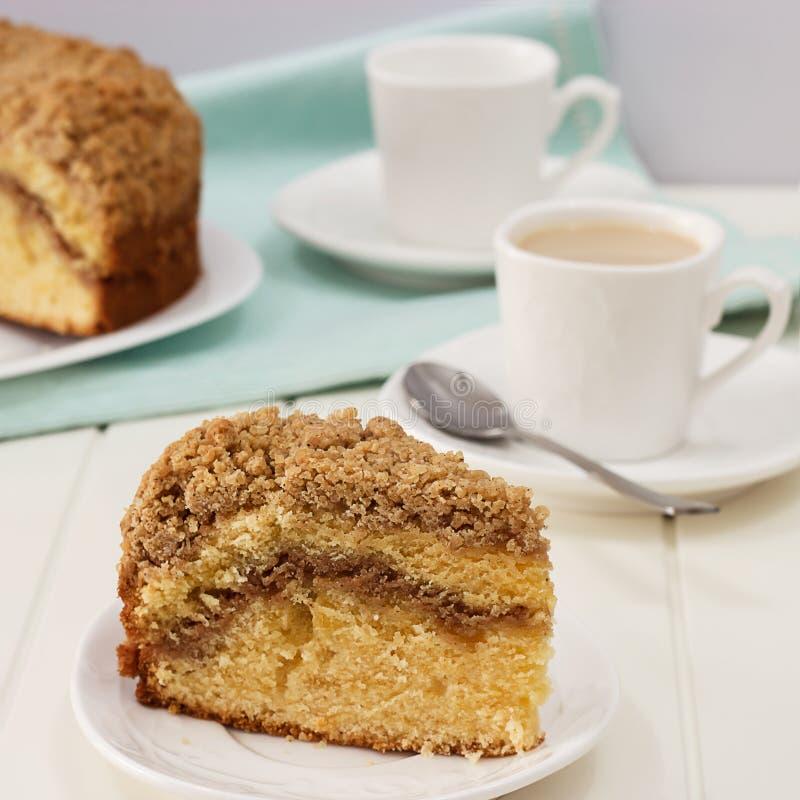 Часть конца-вверх домодельного циннамона крошит торт кофе и чашка чая молока деревянное предпосылки белое квадрат стоковые фотографии rf