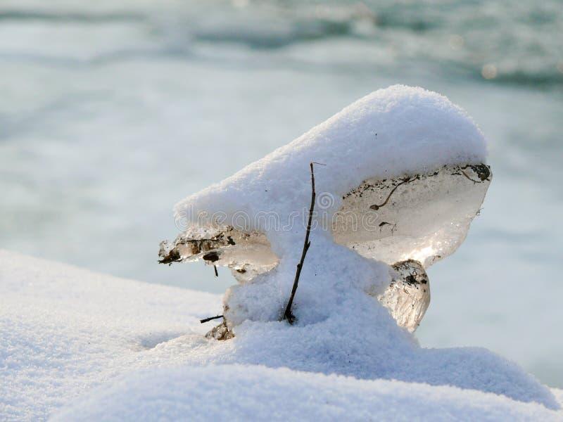 Часть льда покрытая с пушистым снегом во время зимнего времени стоковое фото rf