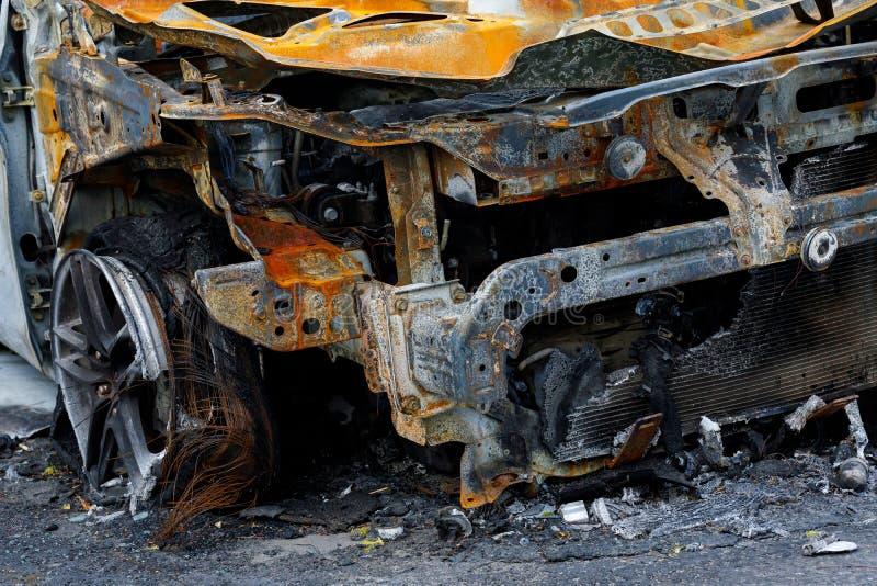 Часть машины после поджога на стоянке возле дома чтобы проиллюстрировать статью о пожаре, бандитизме, страховом событии, потере стоковые фотографии rf