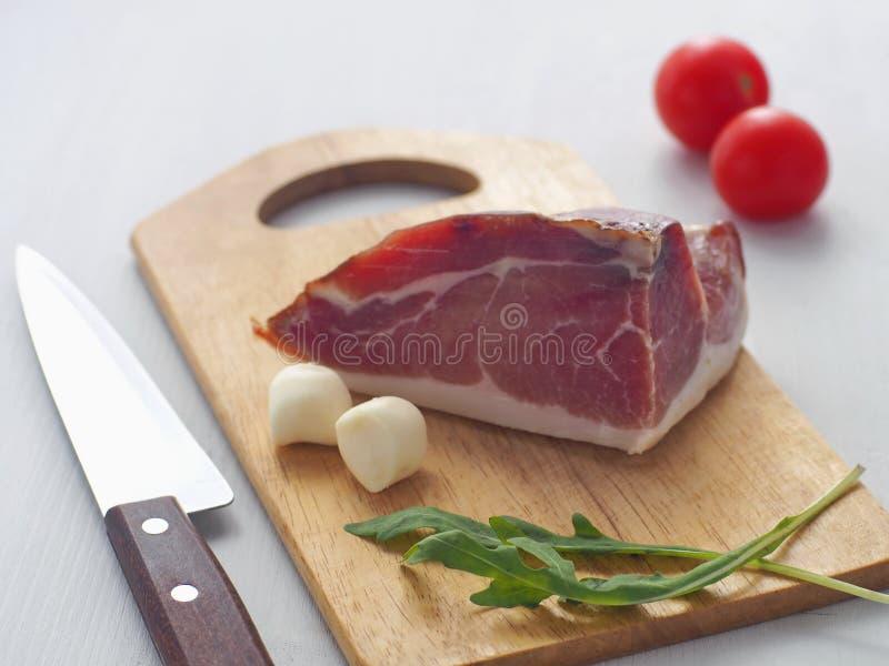 Часть мяса на белой таблице Ветчина, prsut, или испанское jamon с томатами вишни, свежим arugula и моццареллой стоковая фотография rf